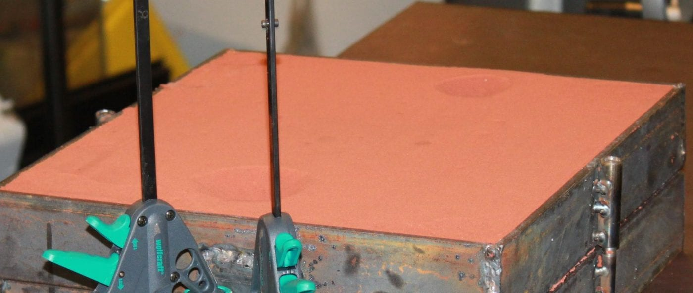 Gjuta metall i sand: Bild på Matare och Stigare med urgröpta hål formade som tratt för metallen.