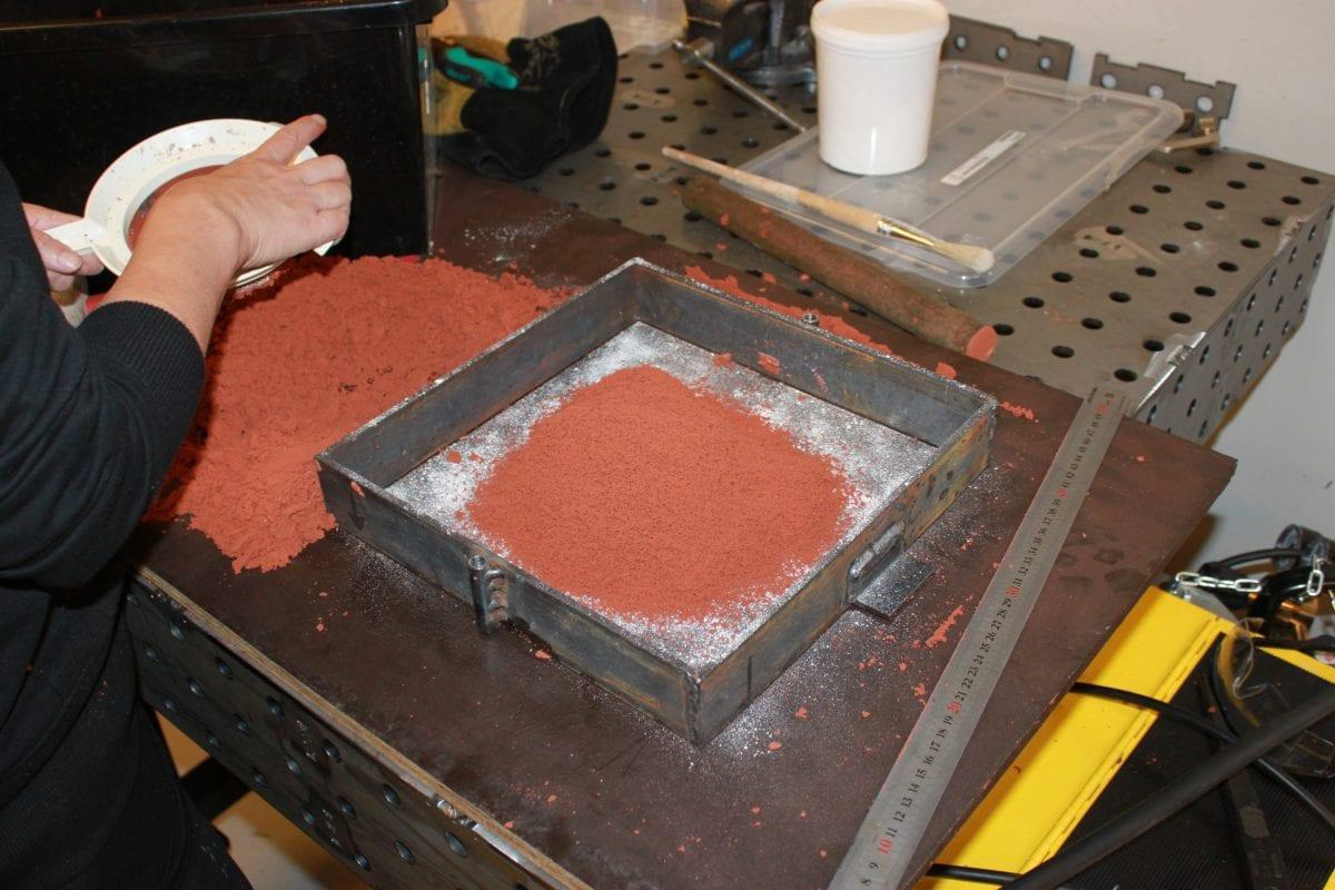 Gjuta metall i sand: Släppmedel och finfördelad sand över avgjutningsformen.