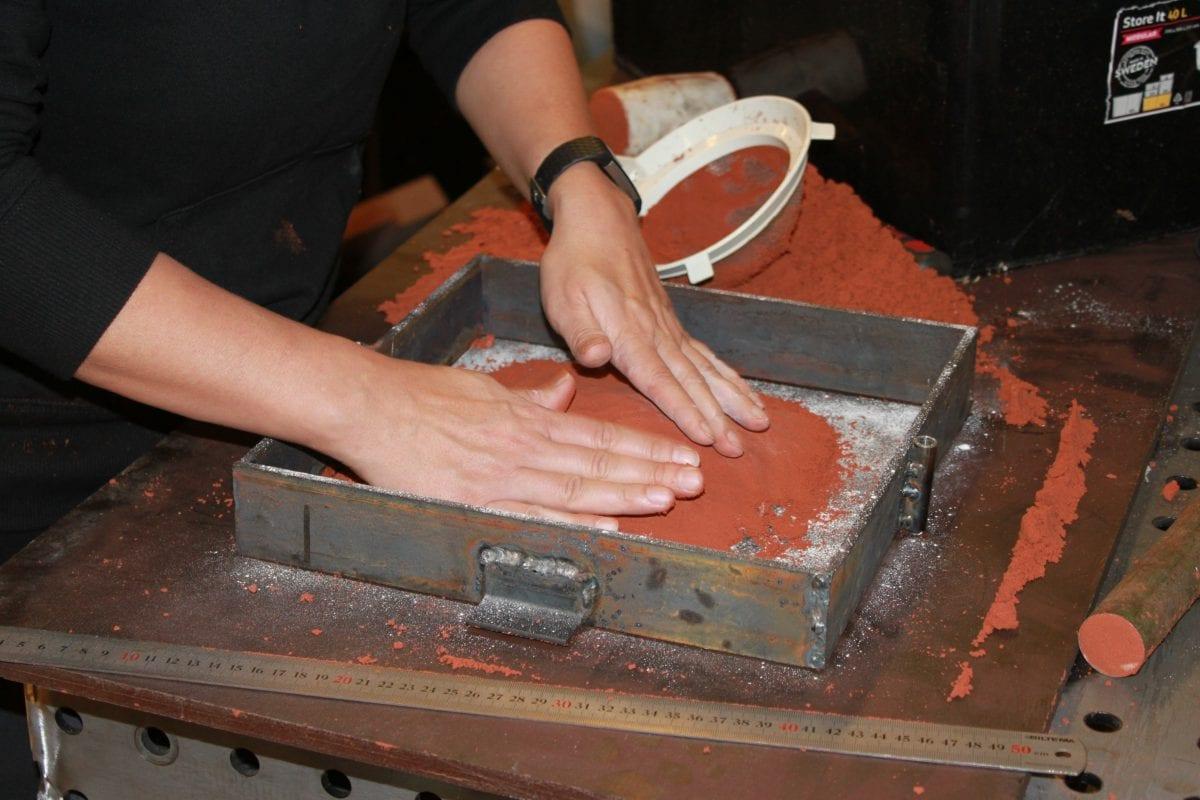 Gjuta metall i sand: Packa försiktigt sanden närmast avgjutningsformen.
