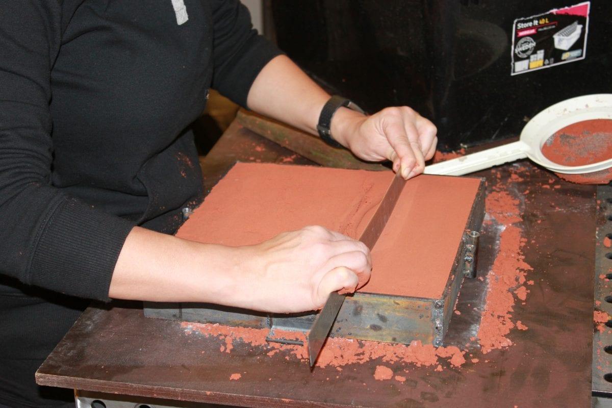 Gjuta metall i sand: Plana ut sanden med ett rakt verktyg.